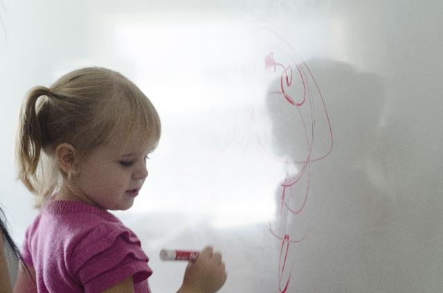 ホワイトボードに絵を描く少女